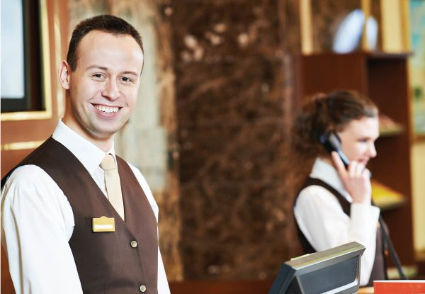 two hotel employees happily working at the front desk