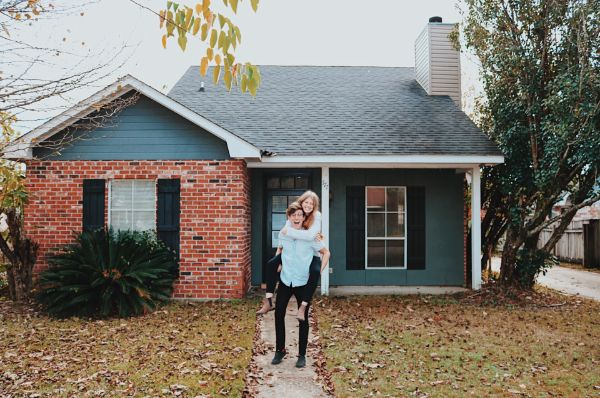 a happy couple standing in front of a house