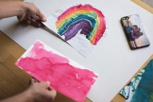a woman looking at her child's rainbow painting