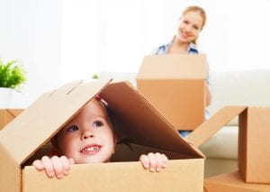 a mother and daughter packing while the girl hides in the box