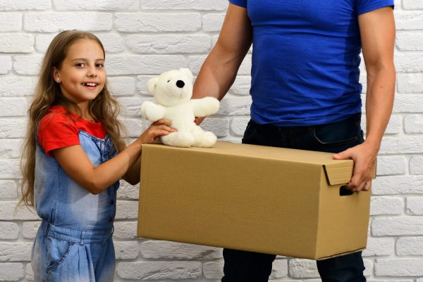 a father carrying a cardboard box while her daughter is holding a teddybear