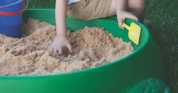 a kid holding a yellow shovel while playing in a green sandbox