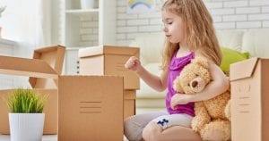a girl holding her stuffed teddy while packing