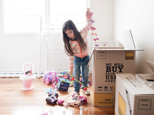 a girl putting her toys inside a tall cardboard box