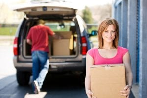 a woman carrying a cardboard box while her husband unloads the rest from the car