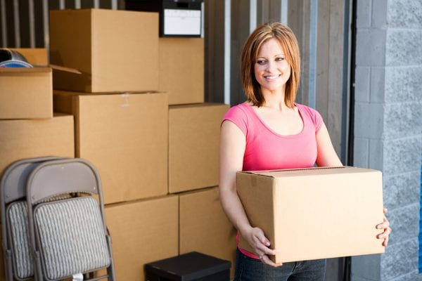 a woman carrying a cardboard box at her storage unit