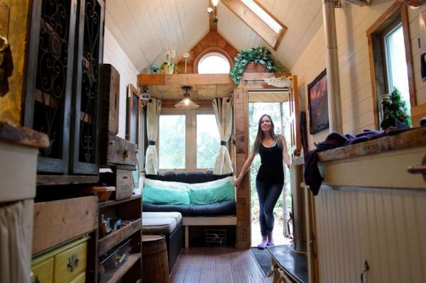 a woman walking into her tiny home
