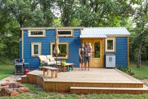 a family standing at the front yard of their tiny home