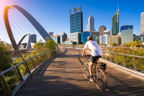a man cycling in the city of perth
