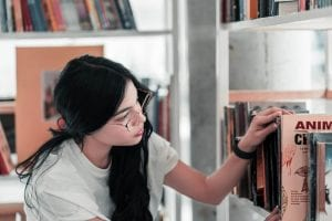 a student choosing books to read in the library