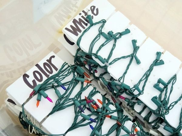 Christmas lights wrapped around white cardboard bobbins