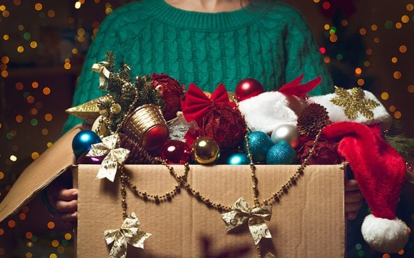 A woman in a sweater carrying a box of christmas ornaments