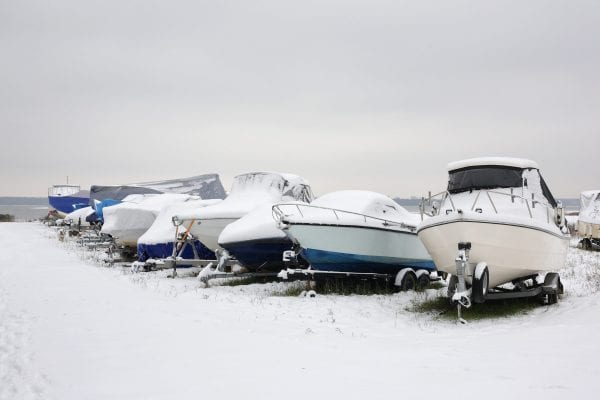 A line of boats parked outdoors in a blizzard