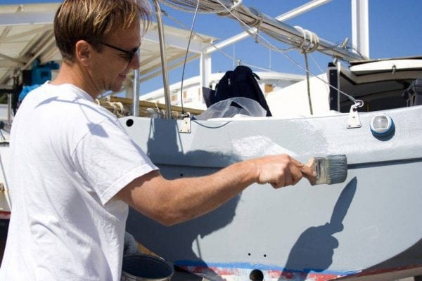 A man using a paint brush to paint his boat grey