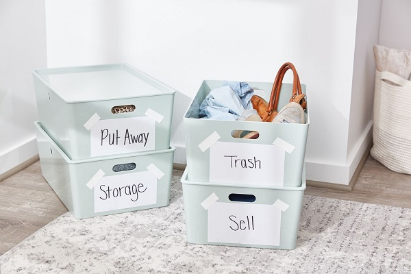Labeled plastic storage containers on the floor